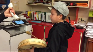 Jerome Whiteknife, grade 4 student, plays the drum and sings to students, parents and staff during morning announcements as a way to open minds.
